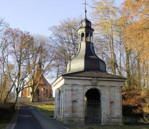 Das barocke Brunnenhaus über der Blutquelle in Burgwindheim, dahinter die Blutskapelle (Foto: Werner Rosenzweig)