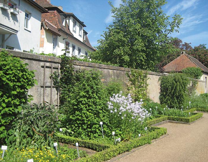 Der Fuchsgarten ist von hohen Mauern umgeben, die Beete sind streng geometrisch angelegt und mit Buchshecken eingefasst.