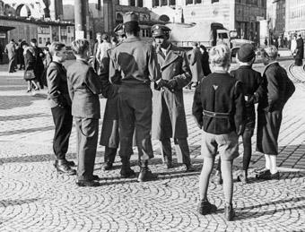 Besatzungssoldaten umringt von Kindern vor dem Münchner Hauptbahnhof, Oktober 1946