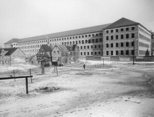 """Der 1939 begonnene Neubau für das städtische Krankenhaus rechts der Isar kurz nach der Vollendung des Rohbaus. Die Kleinhausgruppe In der Grube 28 und 29 bildet vor diesem überdimensionierten Hintergrund nur noch den """"schäbigen Rest"""" der einstigen Grubenbebauung, Aufnahme 1941. (Foto: Stadtarchiv München)"""