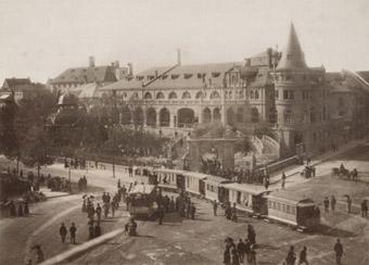 Der Löwenbräukeller im Jahr 1885. Den Stiglmaierplatz queren ein Wagen der Pferdetrambahn und ein Zug der Dampftrambahn, die von hier aus nach Nymphenburg fuhr.