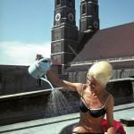 Badenixe in einer Badewanne mit Gießkanne auf einem Dachgarten in der Mittagspause. Im Hintergrund die Türme der Frauenkirche. Juli 1962