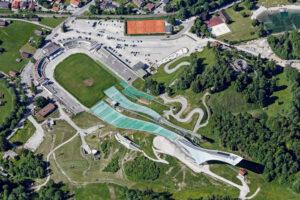 Die Größenverhältnisse aus der Luft: Auch die in jüngerer Zeit errichteten modernen Skischanzen münden in das denkmalgeschützte Stadion aus dem Jahr 1936.