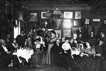 """Eine Abendgesellschaft im """"Simplicissimus"""" aus dem Jahr 1909. In der Mitte mit erhobenem Glas die legendäre Wirtin Kathi Kobus."""